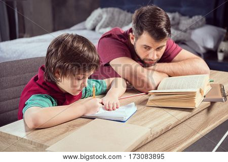 side view of father looking at concentrated son doing homework