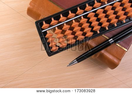 Pen and abacus over old vintage book for with copy space on wooden table. Vintage book for note with pen and abacus for calculate.
