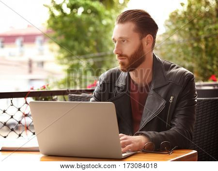 Handsome young man with laptop at cafe