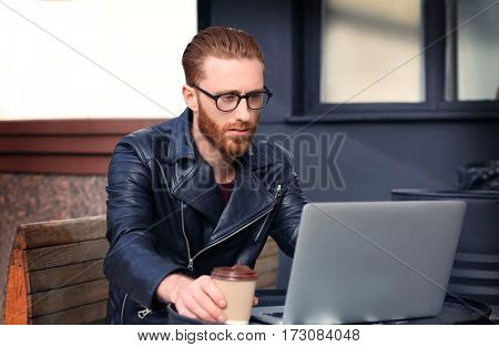 Handsome young man working on laptop outdoors
