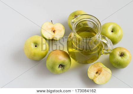 Source of natural vitamins. Small green apples and a glass jug with fresh apple juice on a light background.