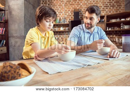 Father and son sitting at wooden table and having breakfast