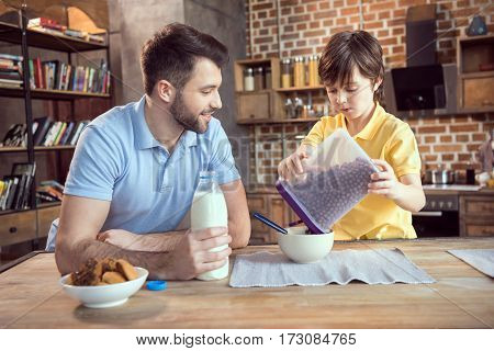 Father and son preparing chocolate corn balls with milk for breakfast