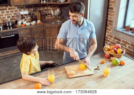 High angle view of happy father and son cutting fruits and drinking fresh juice