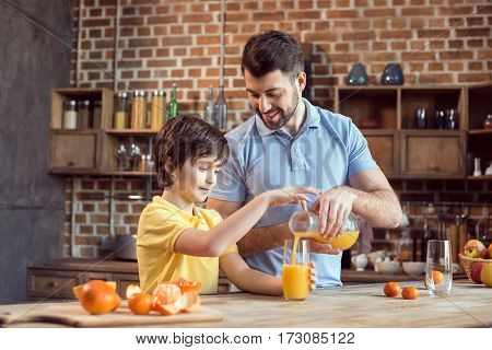 Happy father and son pouring fresh juice in glass