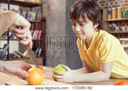Cropped shot of cute smiling son looking at father cutting grapefruit with knife