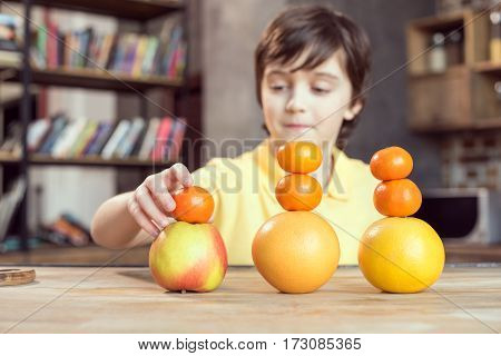 Cute little boy playing with fresh fruits on table