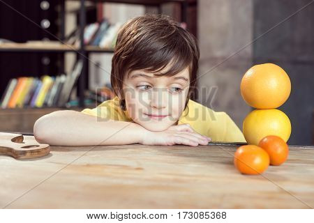 Cute smiling boy leaning at table and looking at fresh fruits