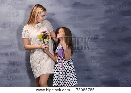 Cute little girl giving mother flowers and present, on color background. Mother's day concept