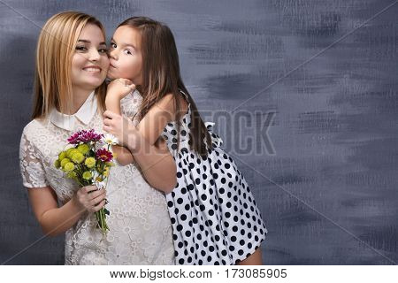 Beautiful young woman with bouquet and her daughter near color wall. Mother's day concept