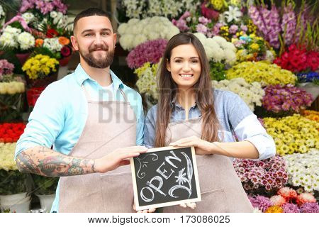 Male and female florists holding board with inscription OPEN in flower shop