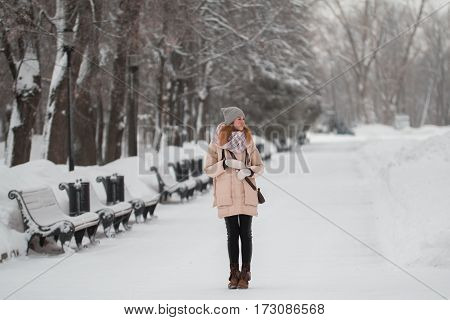 Cute young girl with red hair standing in winter snow park, telephoto