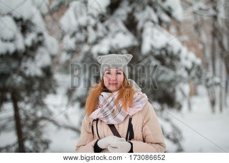 Pretty young girl with red hair standing in winter park near snow pines, telephoto