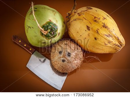 three different coconuts with machete on table top view