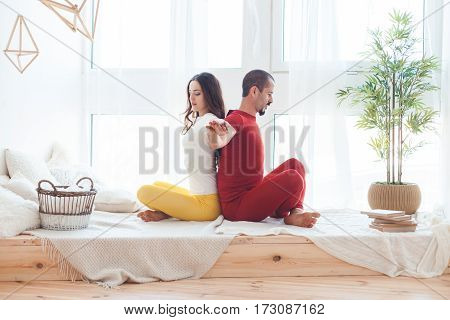 Man and woman practicing yoga at home.