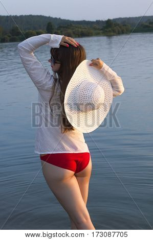 white woman in sun hat posture back on beach lake