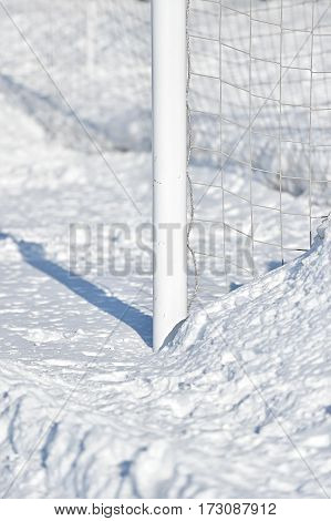 Detail with a soccer goalpost covered by snow