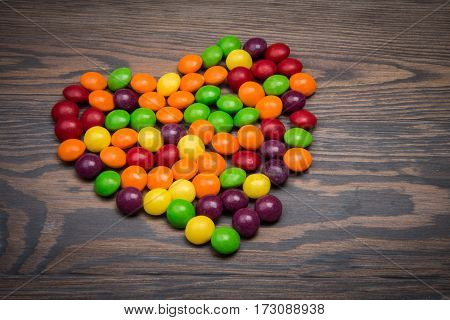 Heart Made Of Colorful Candy On A Wooden Table. Vignette