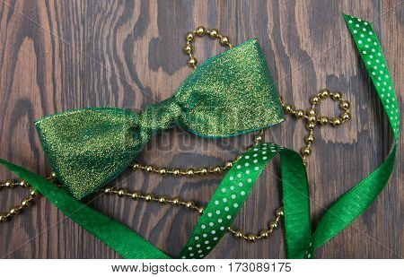 Shiny Green Bow Tie, Satin Ribbon And Gold Beads On Wooden Table
