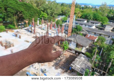 pointing at a building under construction in hand cigarette