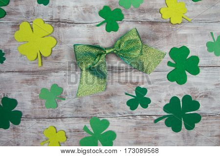 Green Shiny Bow And Shamrocks On Light Wooden Table. Patricks Day