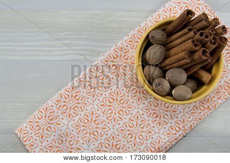 Whole Nutmeg and Cinnamon in Yellow Bowl on Orange Napkin