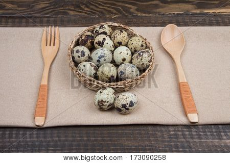 Healthy Breakfast Quail Eggs In Wicker Plate, Fork And Spoon