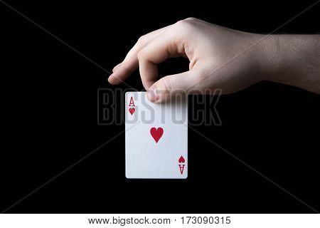 human hand holding the ace of hearts on a black background