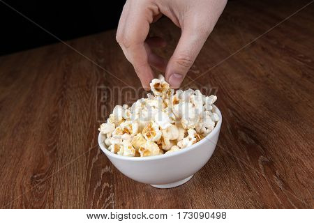 bowl filled with salt popcorn on a wooden table and human hand close up