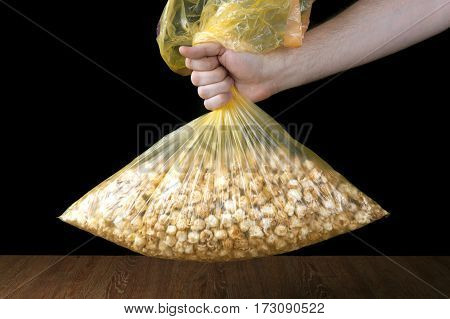 hand holding a plastic bag of popcorn on a black background