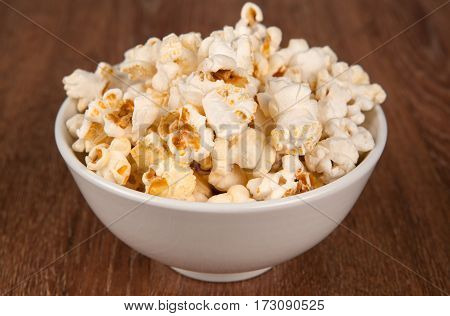 bowl filled with salt popcorn on a wooden table close up