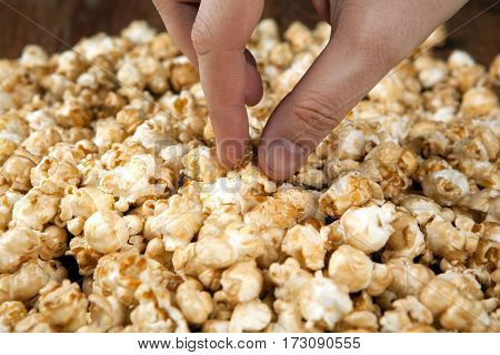 man holds a handful of popcorn in his hands close up