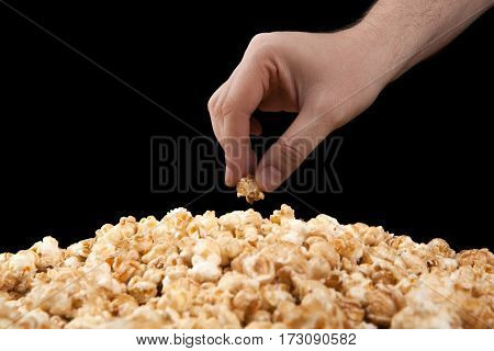 man holds a handful of popcorn in his hand on a black background