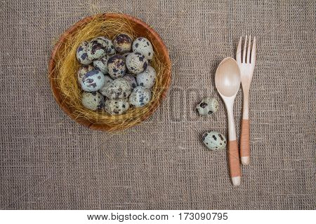 Wooden Fork And Spoon, Bowl Of Quail Eggs On Background Of Sacking