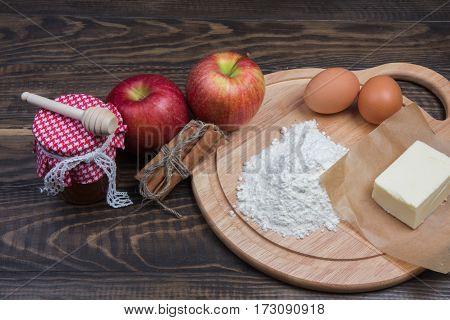 Apples, Flour, Butter, Eggs, And Honey On Dark Wooden Table.