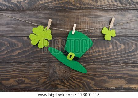 Green Hat And Clover Leaves Hanging On Twine Clothespins