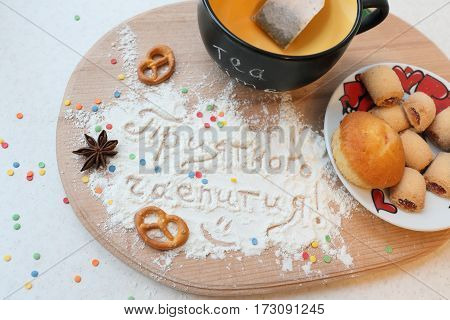 Tea still life with an inscription in Russian Enjoy your tea . Mug with plate of sweets, and the inscription on the sahornoy powder.
