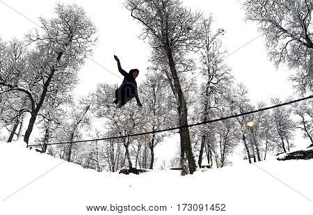 Girl does slack line in snow jumping high up in the air.