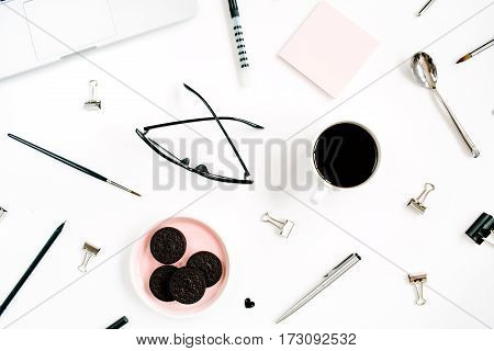 Pale pink stylish home office workspace desk with laptop coffee cookies glasses and office stuff on white background. Flat lay top view. Entrepreneur office concept.