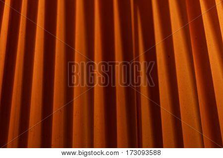 Macro of folded orange textile with background illumination.