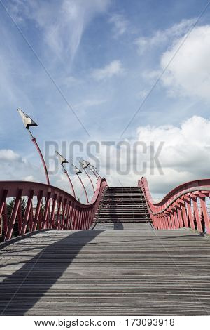 Sinuous stairway with red banister in the blue sky with clouds
