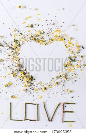 Top view of heart made of flowers petals and love lettering on white for valentine's day holiday