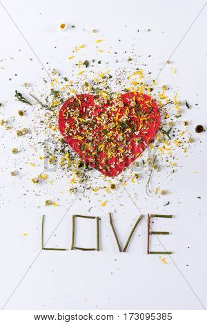 Top view of flowers petals on heart and love lettering on white for valentine's day