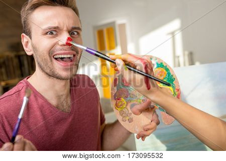 Cropped shot of woman with paintbrush painting nose of her boyfriend holding palette