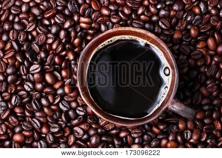 Clay cup with coffee on texture coffee beans.top view