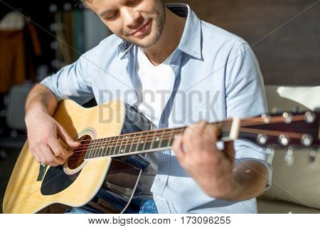 Cropped shot of young handsome man playing guitar and smiling