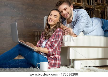 Happy young couple using laptop at home and smiling at camera
