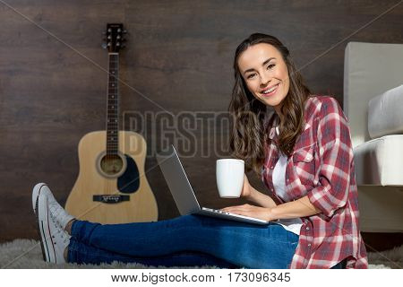 Young woman with tea cup using laptop while sitting on carpet and smiling at camera