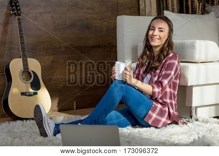 Attractive young woman sitting on carpet with tea cup and smiling at camera