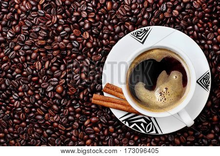 Cup with hot coffee on texture coffe beans.Plate with african ornament.Copy space.top view